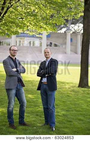Two business partners posing in front of a convention center on a nice spring day under the foliage of a tree