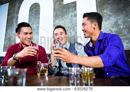 Asian young and handsome group of party people or male friends looking at smart mobile phone in fancy night club