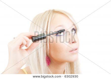 Das Mädchen setzt Mascara.