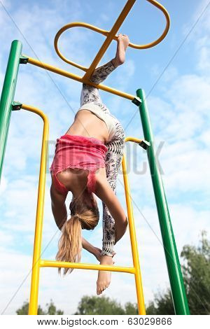 Athletic gymnast working out on metal bars