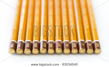 A collection of art graphite pencils of various hardnesses. Each is marked with the degree of hardness.