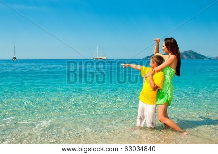 Happy Mom And Son On Sea Beach Looking Into The Distance