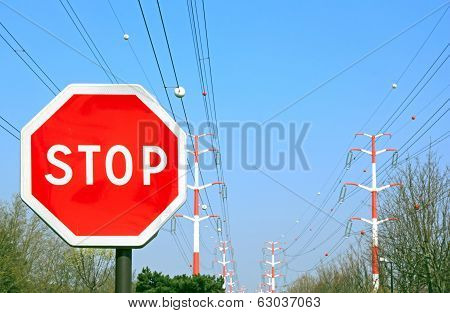 Panel stop, far off high-tension lines, red and white on the horizon (France)