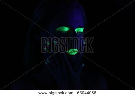 Beautiful Woman Wearing UV Cosmetics Under Black Light