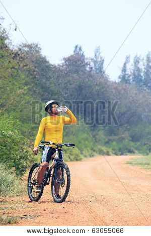 Young Bicycle (cyclist) Man Drinking Fresh Water From Plastic Bottle While Biking Mtb On Dirty Road