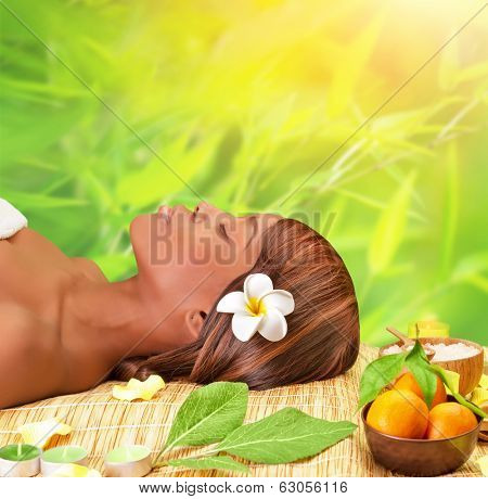 Beautiful young african woman enjoying day spa, lying down on massage table with closed eyes, take medical treatment outdoors, luxury spa resort