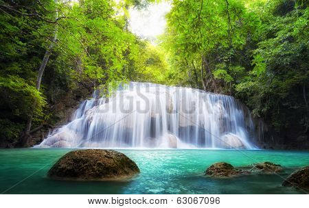 Tropical waterfall in Thailand, nature photography. Fresh water mountain river in wild green jungle forest. Scenic and peaceful Asia nature background of beautiful blue water pool and creek cascade