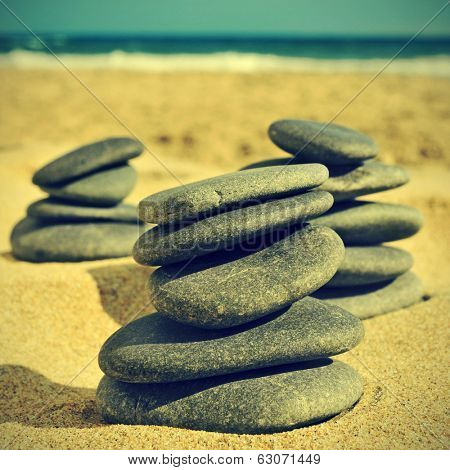 some stacks of stones on a beach, with a retro effect