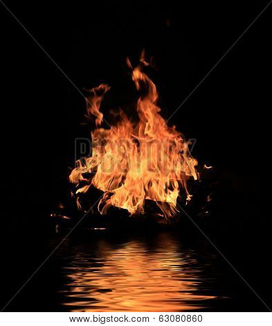 Flame of fire in darkness with water reflection