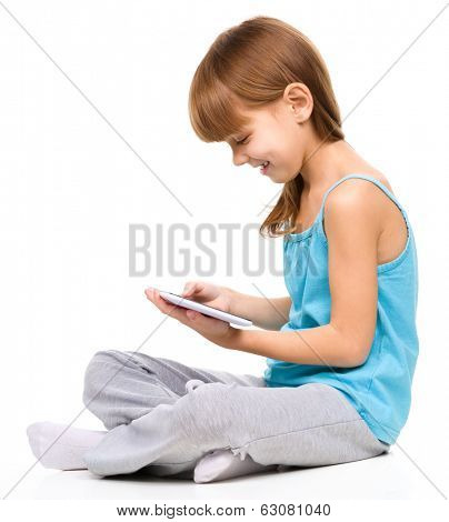 Young girl is using tablet while sitting on floor, isolated over white