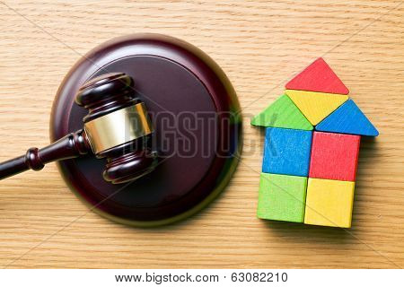 the wooden house and judge gavel on wooden table