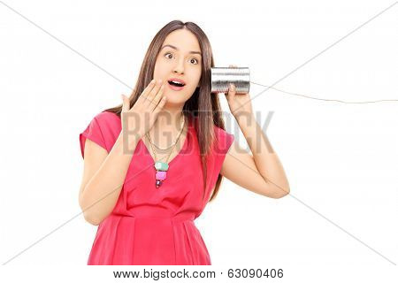 Woman hearing something through a tin can phone isolated on white background