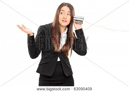 Businesswoman listening through a tin can phone isolated on white background
