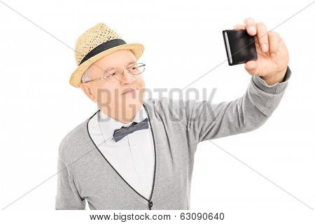 Senior gentleman taking a selfie with cell phone isolated on white background