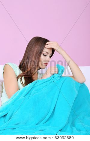 Beautiful young woman sitting on sofa with plaid on pink background