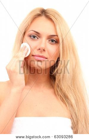 Beautiful young woman with a cotton pad on white background close-up