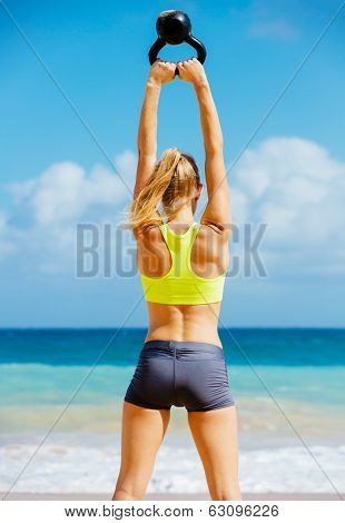 Young attractive woman doing kettle bell exercises outside. Fitness woman working out at the beach.  Fitness Concept.