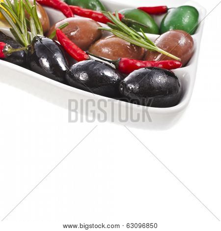 Corner border of olives dish with vegetables, herbs, spices isolated on a white background