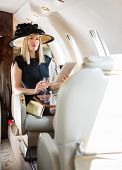 Portrait of rich confident woman using digital tablet while holding drink glass in private jet