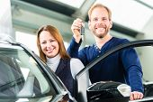 stock photo of beside  - Young man beside a new car in car dealership - JPG