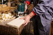 stock photo of joinery  - The carpenter hands when working with electric planer joinery - JPG