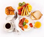 stock photo of croissant  - Breakfast with fried eggs coffee orange juice croissant toasts and fruits - JPG