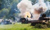 stock photo of military personnel  - German medium half-track armored personnel on the field in the smoke and explosions of shells