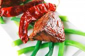 served grilled beef veal fillet entrecote on a white plate with peppers and green peas on long plate