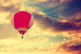 foto of high-rise  - Red Hot Air Balloon Flying over Dramatic Sunset Sky - JPG