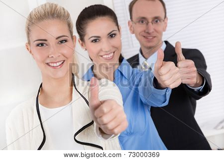 Thumbs up: businessman and two businesswoman - success.