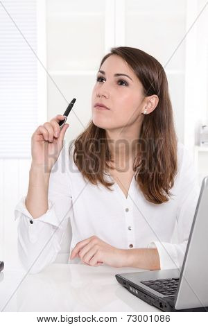Idea: business woman thinking with pen in hand at Office.