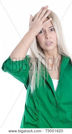 Business pressure: frustrated pretty young blond woman in green blouse is touching her head isolated on white background