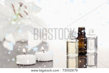 Composite image of snow falling against white orchid with lighted white candles and small phials