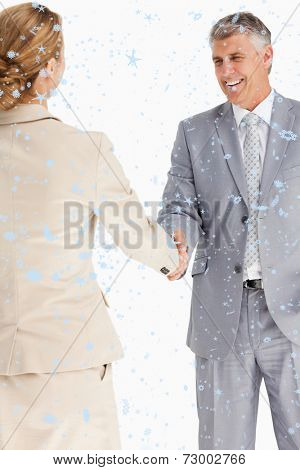 Composite image of Happy business people shaking hands with snow falling