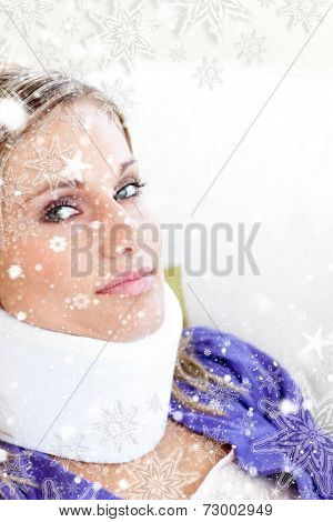 Young woman with a neck brace looking in the camera against snow falling