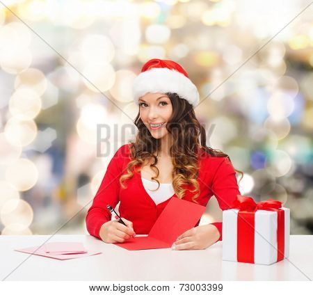 christmas, holidays, celebration, greeting and people concept - smiling woman in santa helper hat with gift box writing letter or sending post card over lights background