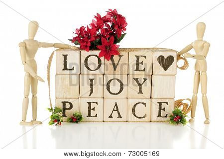 Rustic alphabet blocks arranged to say LOVE, JOY, PEACE.  They are flanked by two wooden mannequins and adorned with Christmas holly and poinsettias.  On a white background.