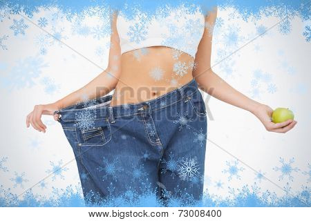 Mid section of slim woman wearing too big jeans holding an apple against snow flake frame in blue