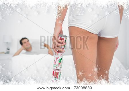 Sexy woman bringing christmas cracker to her partner against fir tree forest and snowflakes