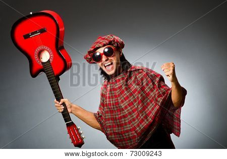 Funny scotsman playing red guitar