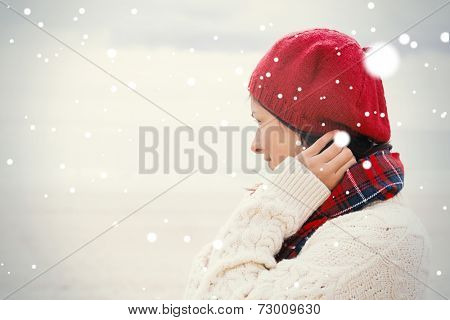 Woman in knitted hat and pullover at beach against snow