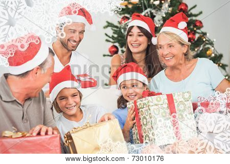 Happy family at christmas swapping gifts against snowflake frame