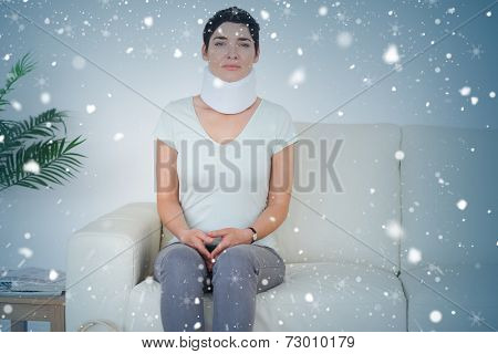 Composite image of sad woman with a surgical collar against snow falling