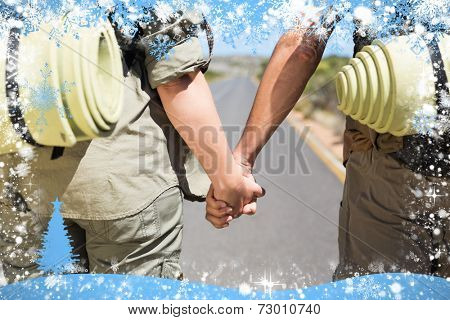 Hitch hiking couple standing holding hands on the road against snow