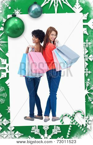 Smiling teenagers looking behind them after shopping against christmas frame