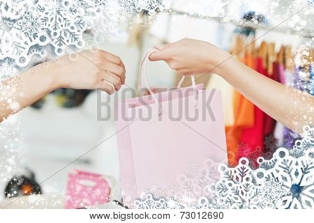 A saleswoman giving a shopping bag to a customer against snow
