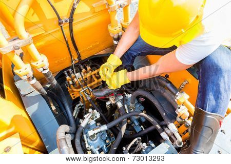 Asian motor mechanic working on construction or mining machinery in vehicle workshop