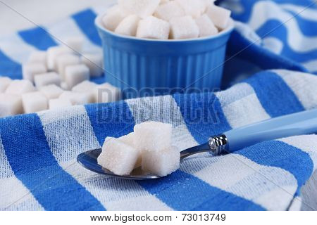 Refined sugar in color bowl on color napkin background