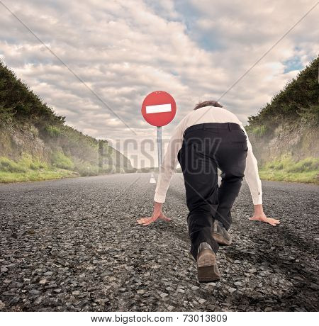 businessman on a road ready to run with No Entry Traffic Road Sign in front