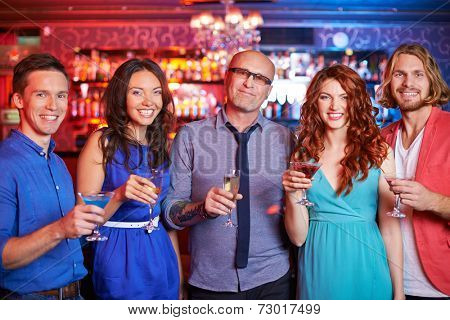 Group of boozing people with drinks looking at camera at party